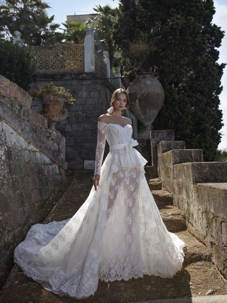 In questa foto una modella indossa un abito da sposa con maniche lunghe in pizzo