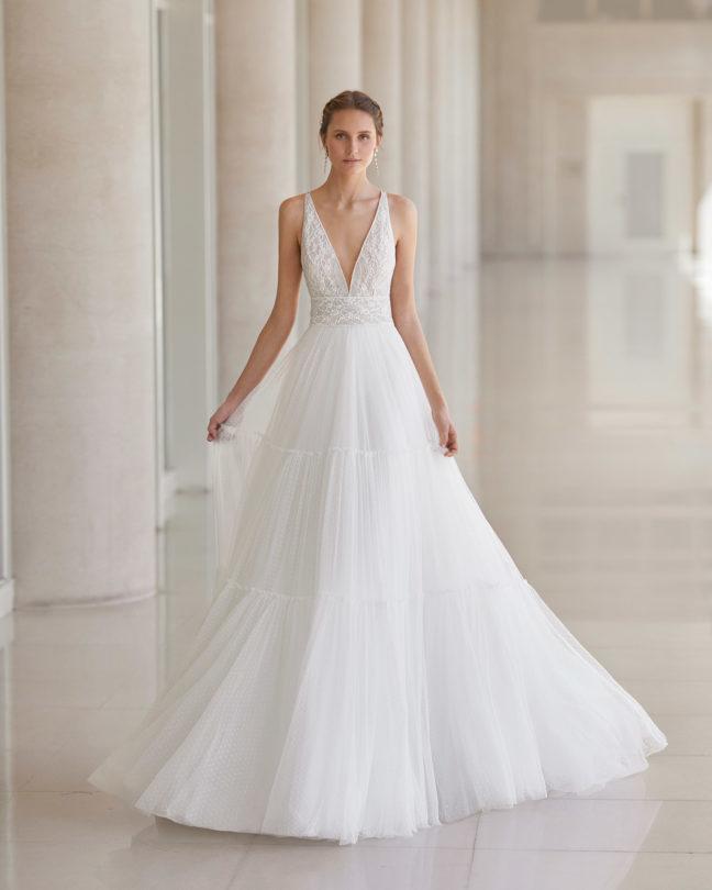 In questa foto una modella indossa un abito da sposa dalla linea ad A di Aire Barcelona