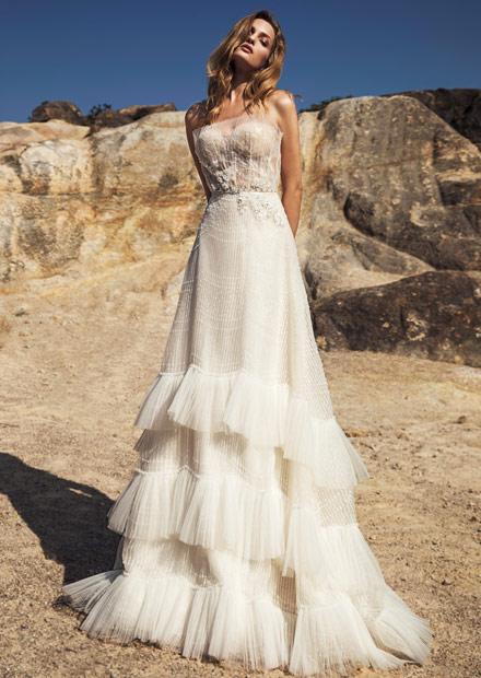 In questa foto una modella indossa un abito da sposa con balze e punti luce perfetto per un matrimonio bordo piscina
