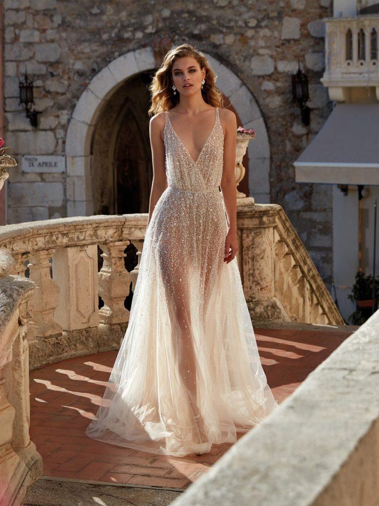 In questa foto una modella indossa un abito da sposa sparkling perfetto per un matrimonio bordo piscina