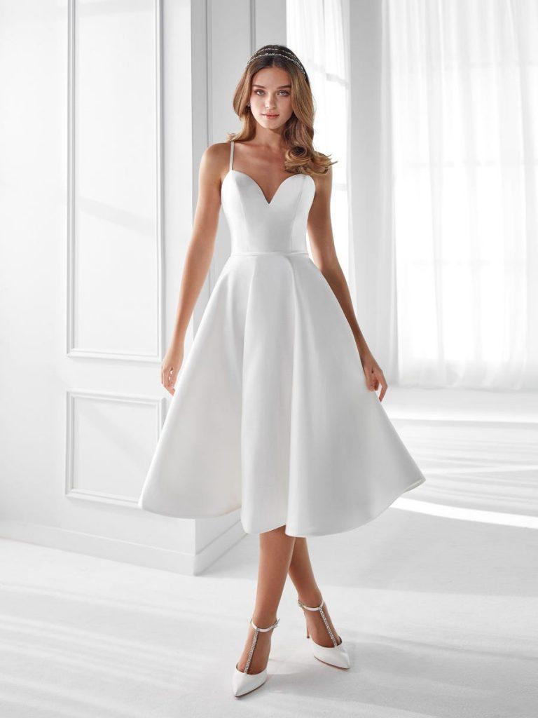 In questa foto una modella indossa un abito da sposa lungo fin sotto il ginocchio di Nicole, perfetto per un rito civile