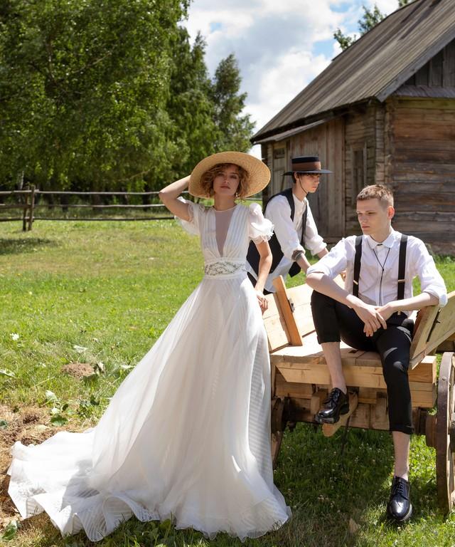 In questa foto una modella indossa un abito da sposa con maniche a palloncino e dalla linea scivolata perfetto per un matrimonio in giardino