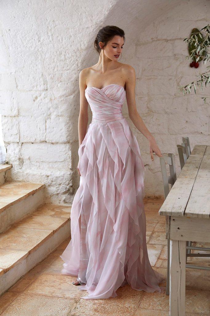 In questa foto una modella indossa un abito da sposa rosa di Blumarine adatto per un matrimonio su un'isola