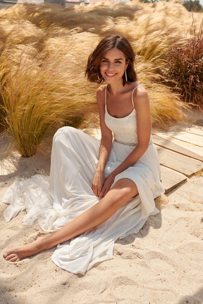 In questa foto una modella indossa un abito da sposa leggero e scivolato, con bretelle sottili, perfetto per un matrimonio in spiaggia