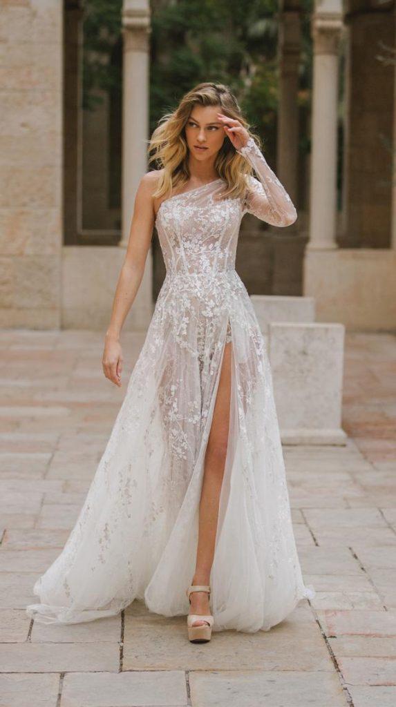 In questa foto una modella indossa un abito da sposa monospalla e con spacco ricamato in pizzo floreale, adatto per un matrimonio in villa