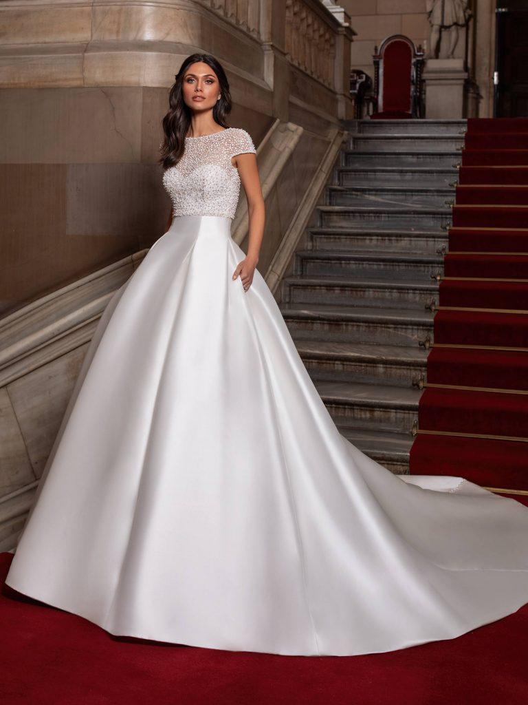 In questa foto una modella indossa un abito da sposa in mikado di Pronovias