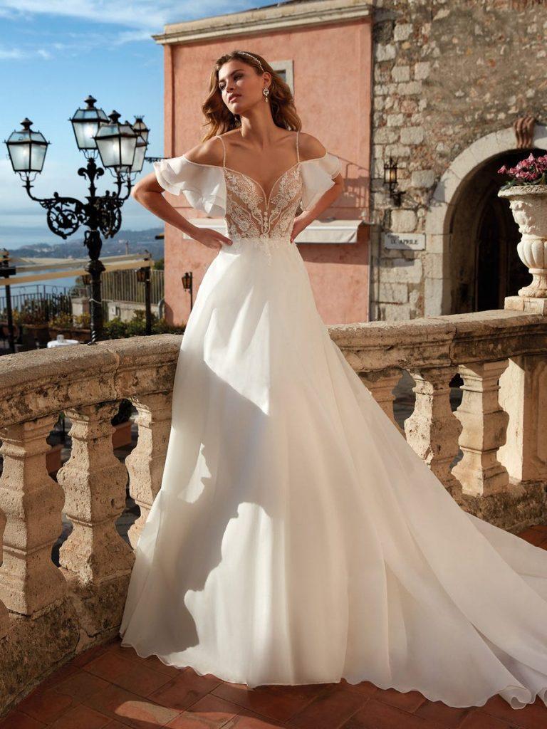In questa foto una modella indossa un abito da sposa in organza di Nicole Milano