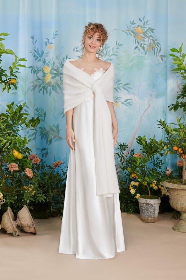 In questa foto una modella indossa un abito da sposa sottoveste, con lunga stola ton sur ton annodata sul petto, perfetto per una donna matura