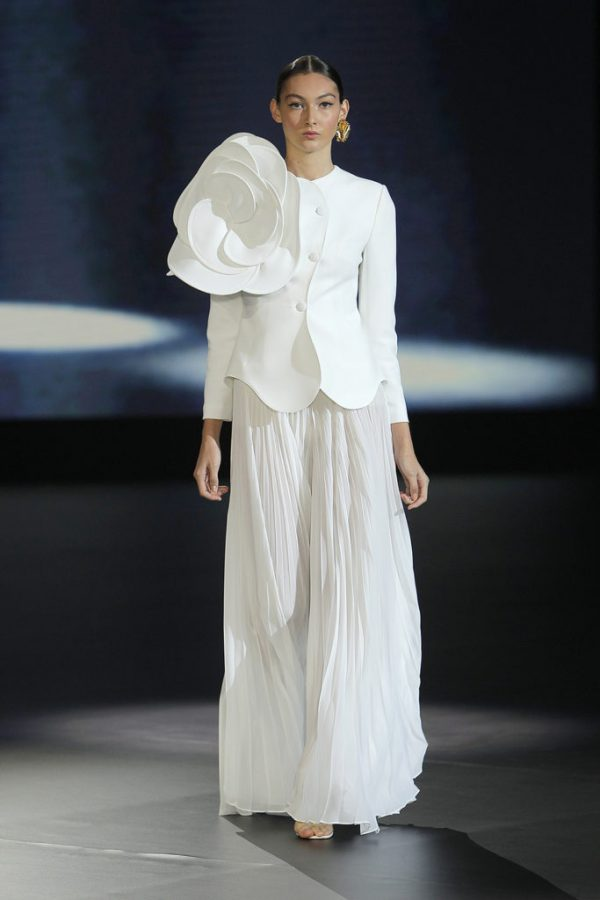 In questa foto una modella indossa un abito da sposa composto da giacca con maxi decorazione floreale e gonna lunga plissettata, ideale per una sposa over 50