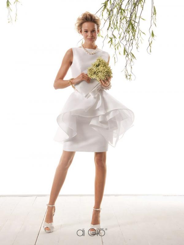In questa foto una modella indossa un abito da sposa corto di Le Spose di Giò