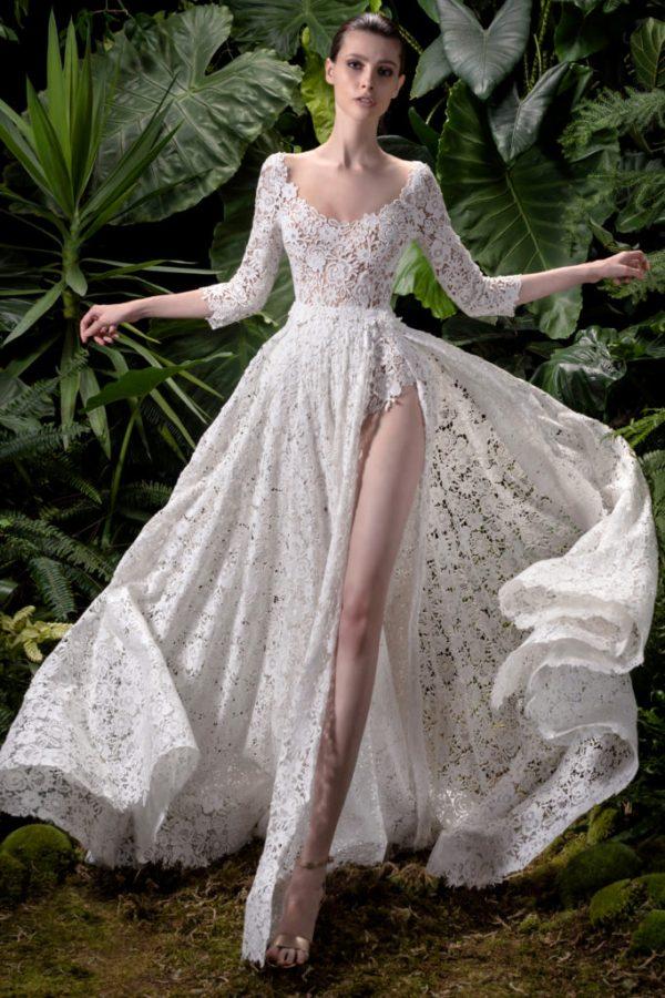 In questa foto una modella indossa un abito da sposa in pizzo con spacco di Andrea Sedici