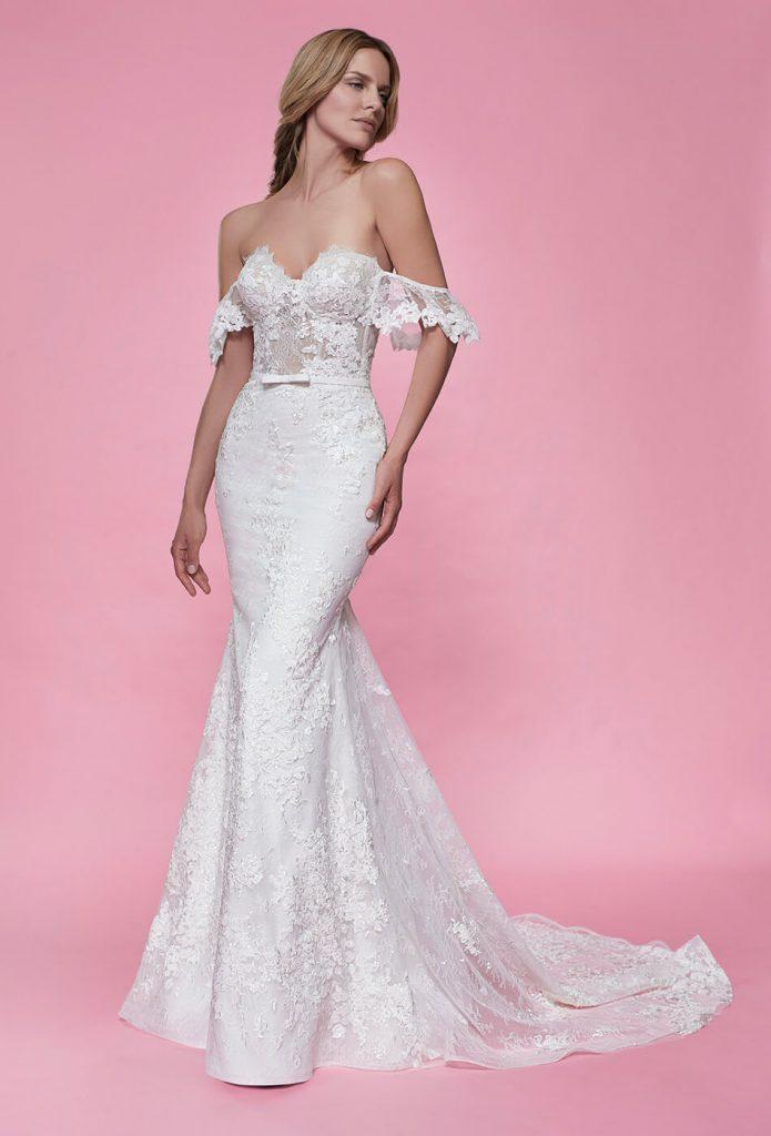In questa foto una modella indossa un abito da sposa sexy a sirena in pizzo, con bustier steccato di Maison Signore