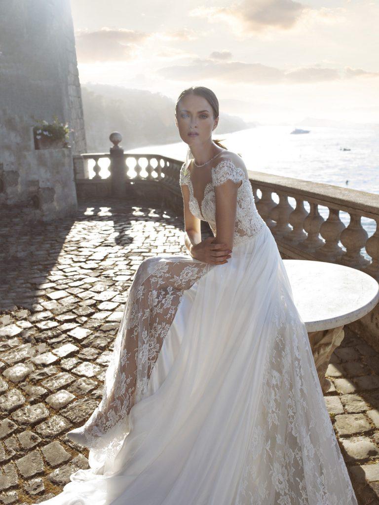 In questa foto una modella indossa un abito da sposa in pizzo di Michela Ferriero