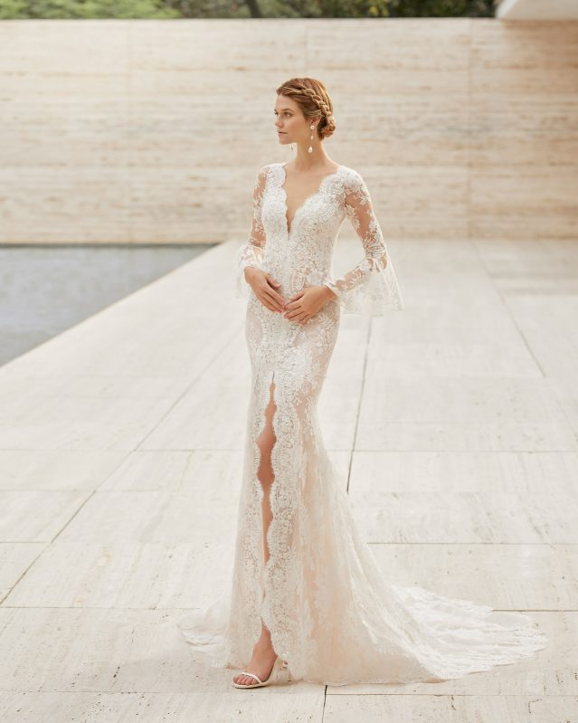 In questa foto una modella indossa un abito da sposa in pizzo con spacco e scollatura a V di Rosa Clarà