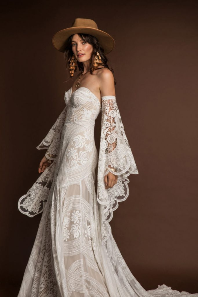 In questa foto una modella indossa un abito da sposa in stile boho perfetto per un matrimonio in primavera