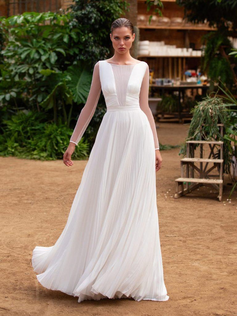 In questa foto una modella indossa un abito da sposa con maniche lunghe leggere e trasparenti, adatto per nozze primaverili