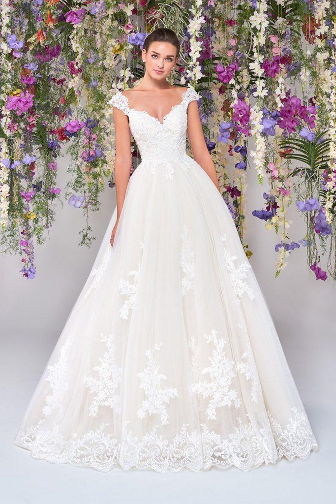 In questa foto una modella indossa un abito da sposa principessa con ricami floreali in pizzo di Atelier Emé