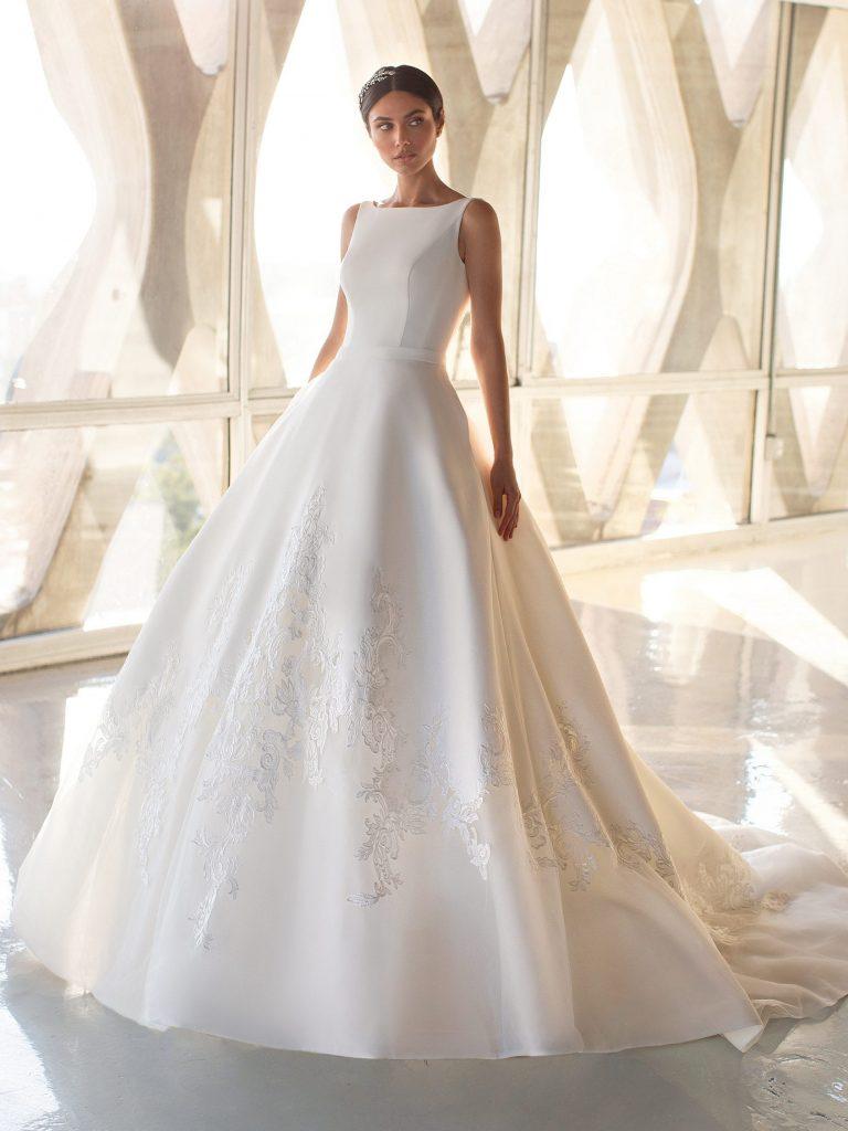 In questa foto una modella indossa un abito da sposa con scollatura a barchetta di Pronovias