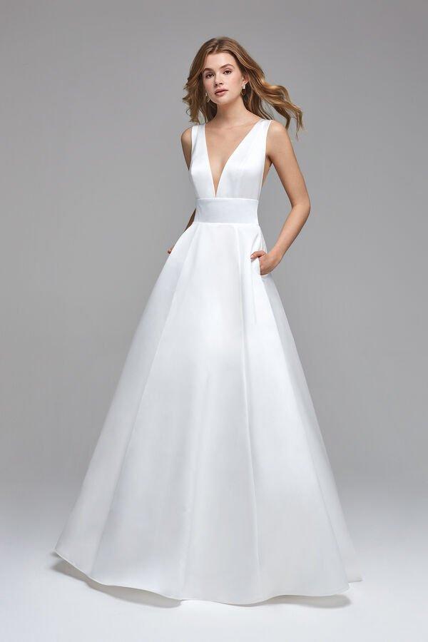In questa foto una modella indossa un abito da sposa in raso di Atelier Emé