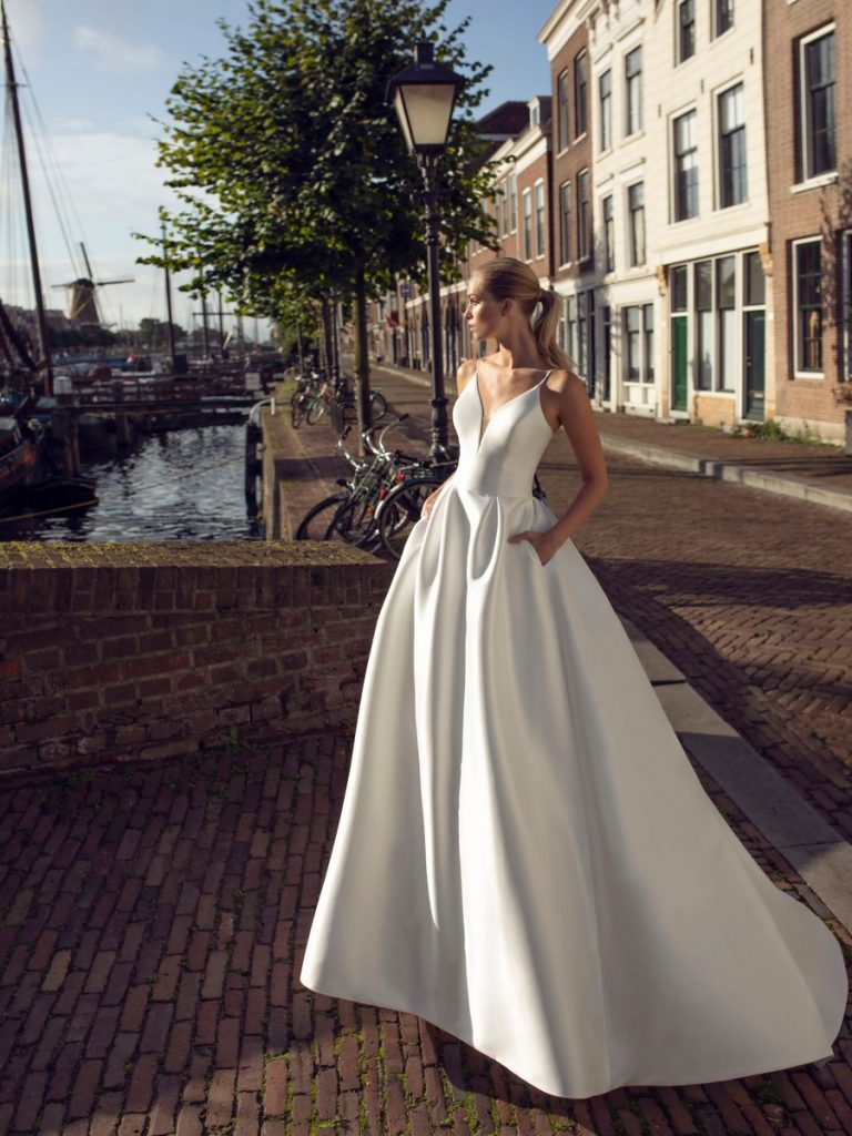 In questa foto una modella indossa un abito da sposa modello redingote di Modeca