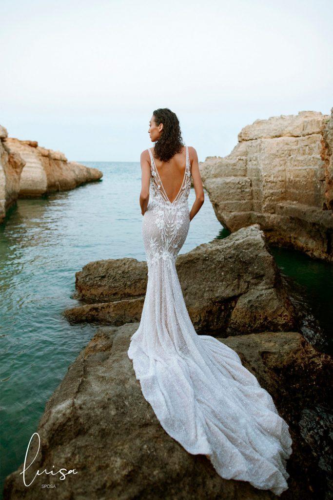 In questa foto una modella indossa un abito da sposa con scollatura a V sulla schiena della collezione Luisa Sposa