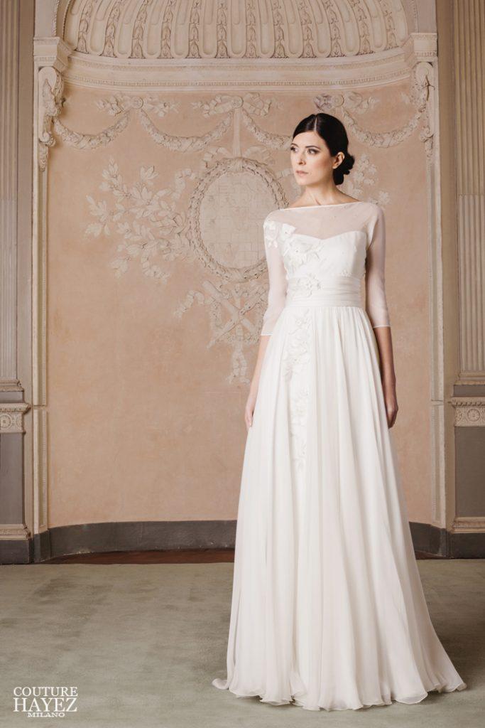 In questa foto una modella indossa un abito da sposa scivolato con manica tre quarti di Couture Hayez