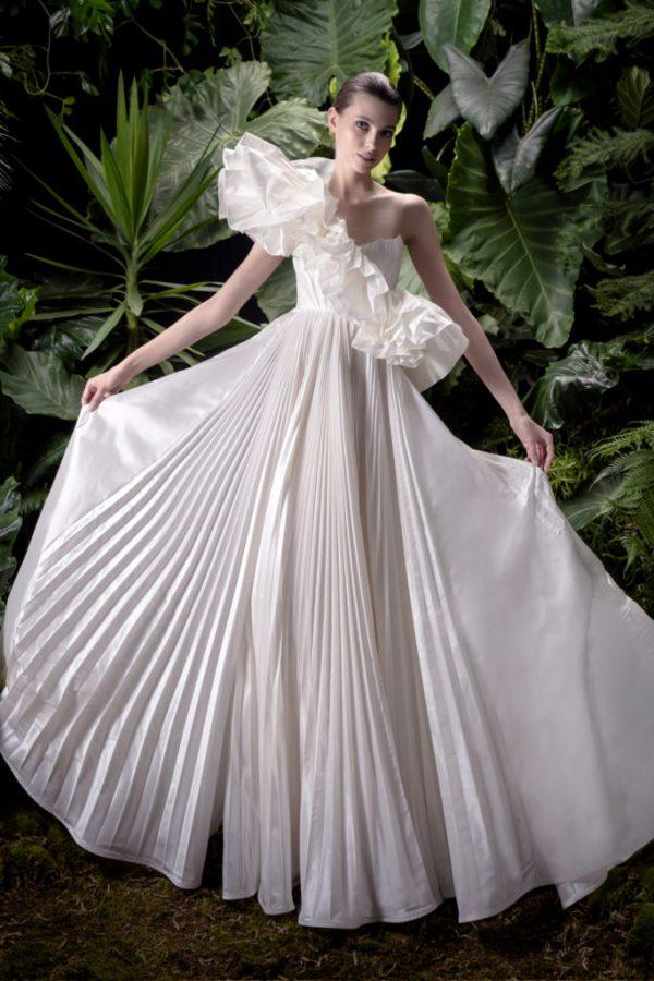 In questa foto una modella indossa un abito da sposa con scollatura asimmetrica di Andrea Sedici