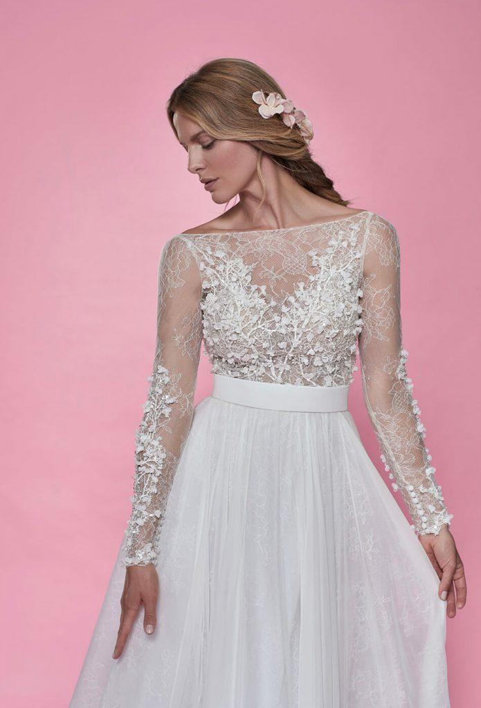 In questa foto una modella indossa un abito da sposa con scollo a barchetta di Maison Signore