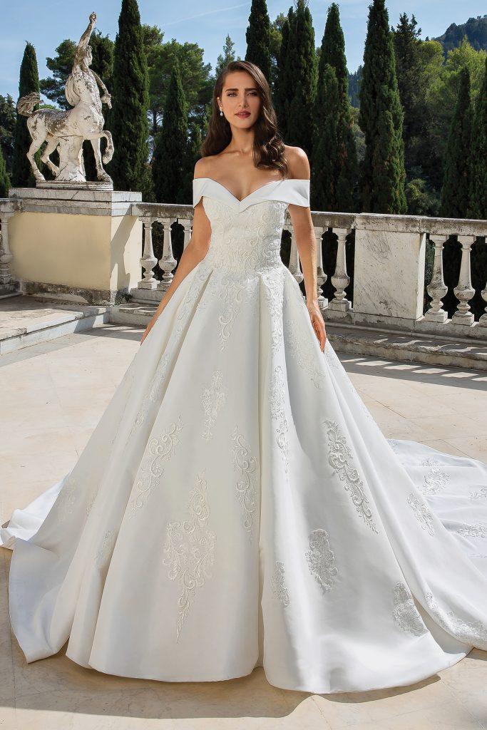 In questa foto una modella indossa un abito da sposa con scollatura off-shoulder di Justin Alexander