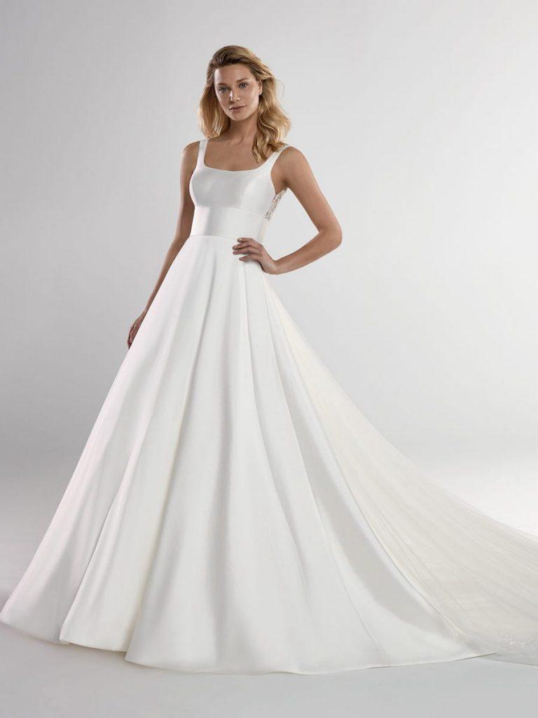 In questa foto una modella indossa un abito da sposa con scollatura quadrata di Nicole