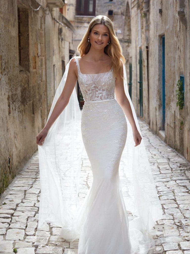 In questa foto una modella indossa un abito da sposa con scollatura quadrata di Nicole Milano