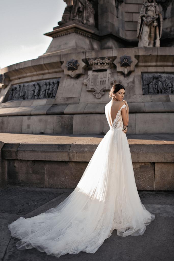 In questa foto una modella indossa un abito da sposa con scollatura a V sulla schiena di Gali Karten