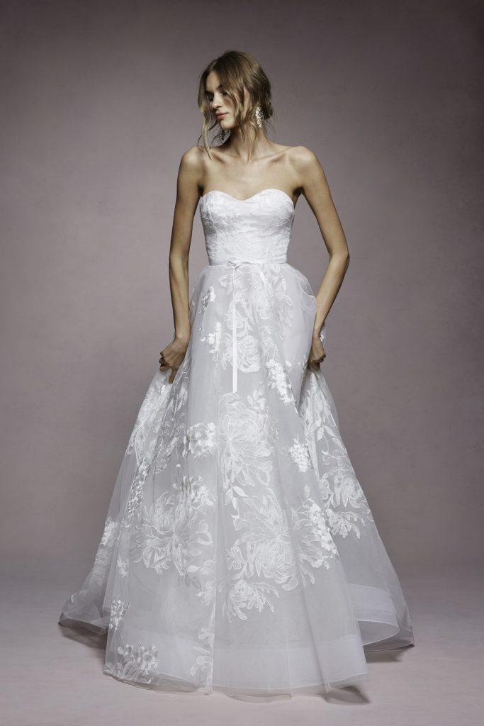 In questa foto una modella indossa un abito da sposa con scollatura a semicuore di Marchesa