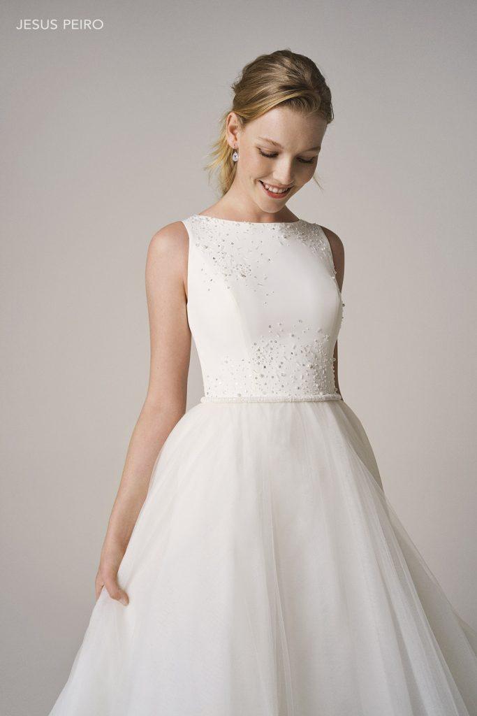 In questa foto una modella indossa un abito da sposa con scollatura Sabrina di Jesus Peiro