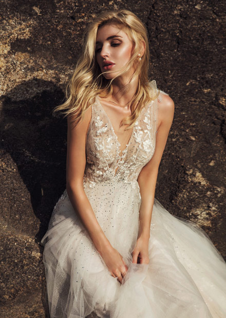 In questa foto una modella indossa un abito da sposa con scollo a V di AnnyLin Bridal