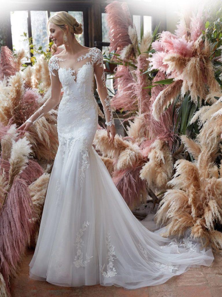 In questa foto una modella indossa un abito da sposa semisirena di Nicole Milano