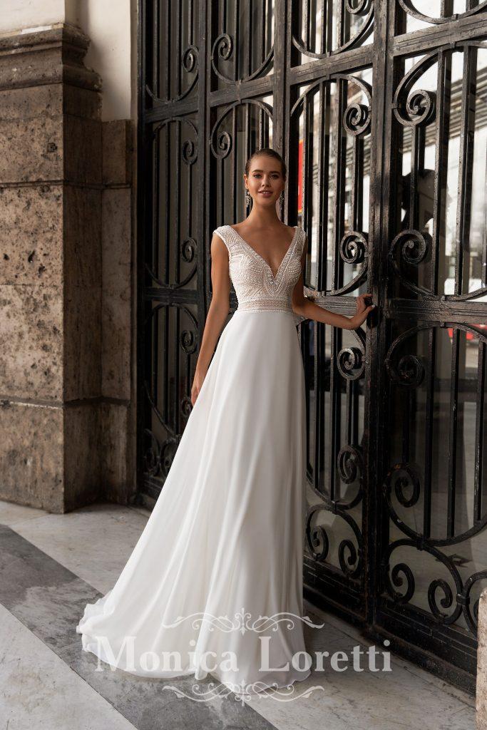 In questa foto una modella indossa un abito da sposa semplice di Monica Loretti