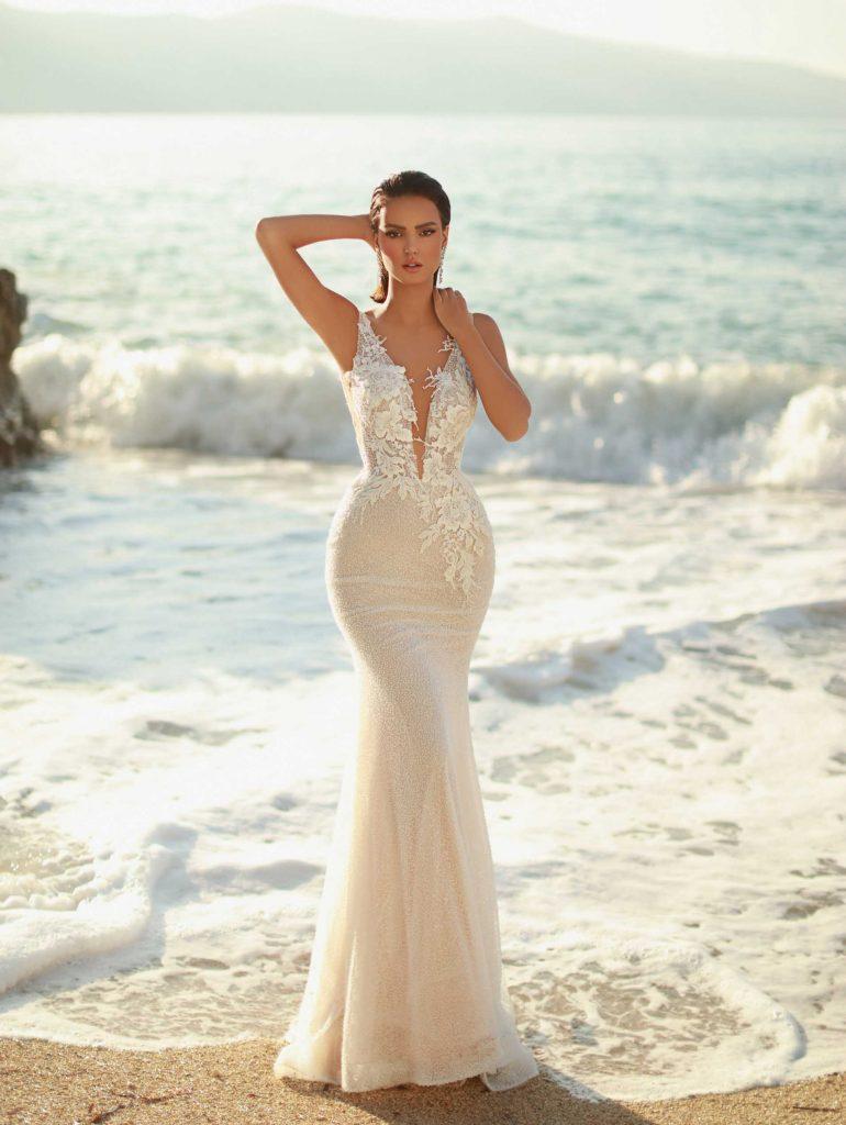 In questa foto una modella in riva al mare indossa un abito da sposa a sirena di Maison Signore