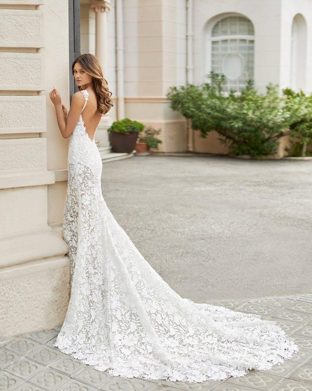 In questa foto una modella indossa un abito da sposa a sirena in pizzo e con strascico di Rosa Clarà