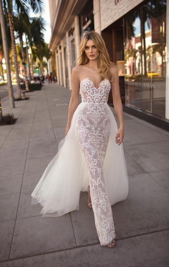 In questa foto una modella passeggia indossando un abito da sposa a sirena in pizzo con sopragonna di Berta Bridal