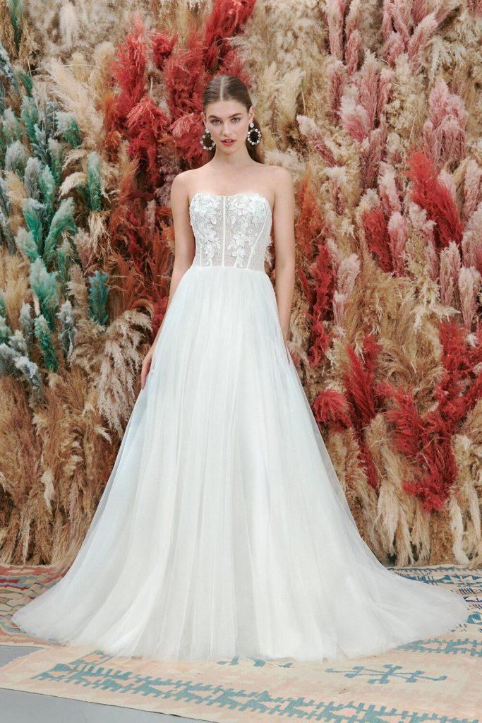 In questa foto una modella indossa un abito da sposa scivolato con gonna in tulle di Atelier Emé