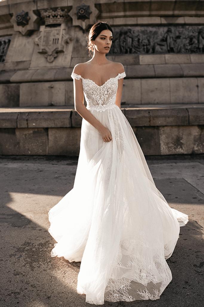 In questa foto una modella indossa un abito da sposa scivolato, ideale per le spose più basse che devono slanciare la propria figura