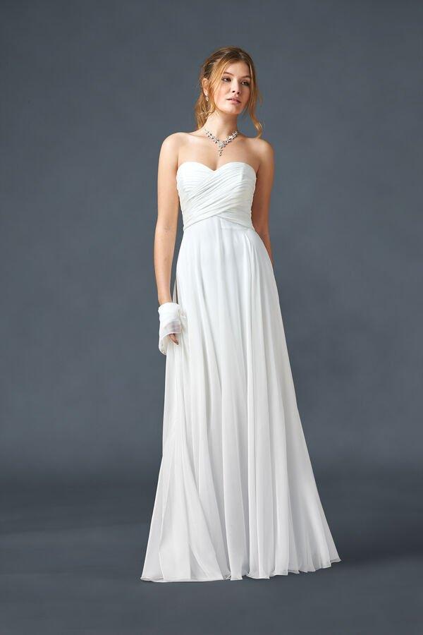 In questa foto una modella indossa un abito da sposa stile impero in chiffon con scollatura a cuore della linea Atelier Emé