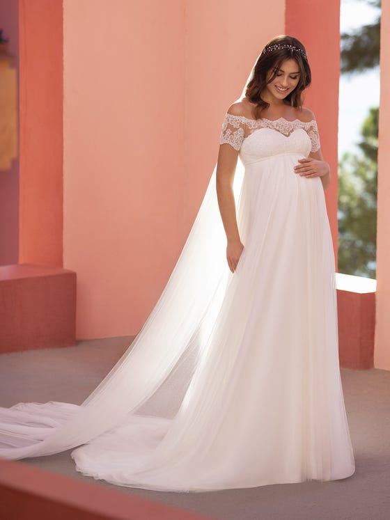 In questa foto una modella indossa un abito da sposa premaman in stile impero