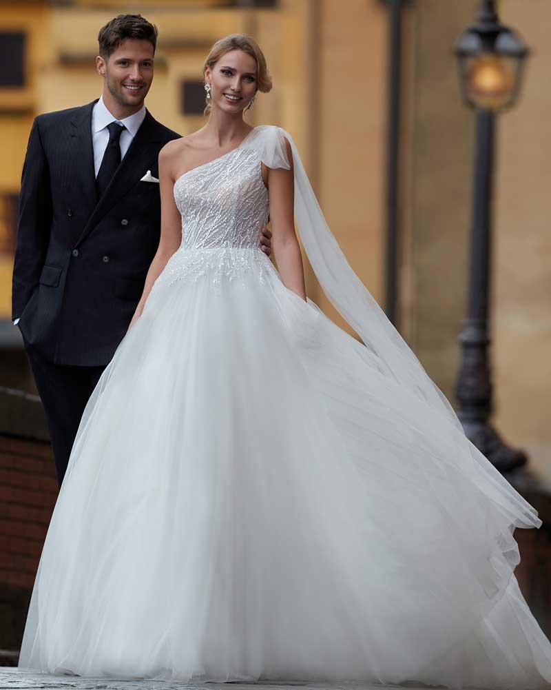 In questa foto una modella indossa un abito da sposa monospalla di Nicole Milano