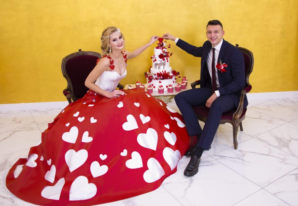 In questa foto gli sposi di Adele Vasilache con la wedding cake a tema San Valentino