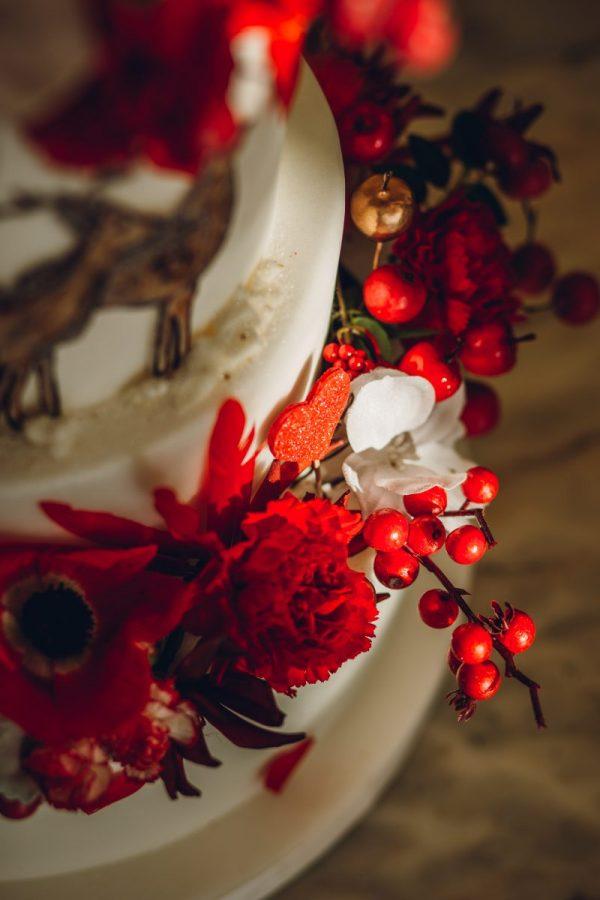 In questa foto il dettaglio di una wedding cake a tema San Valentino con decorazioni floreali rosse