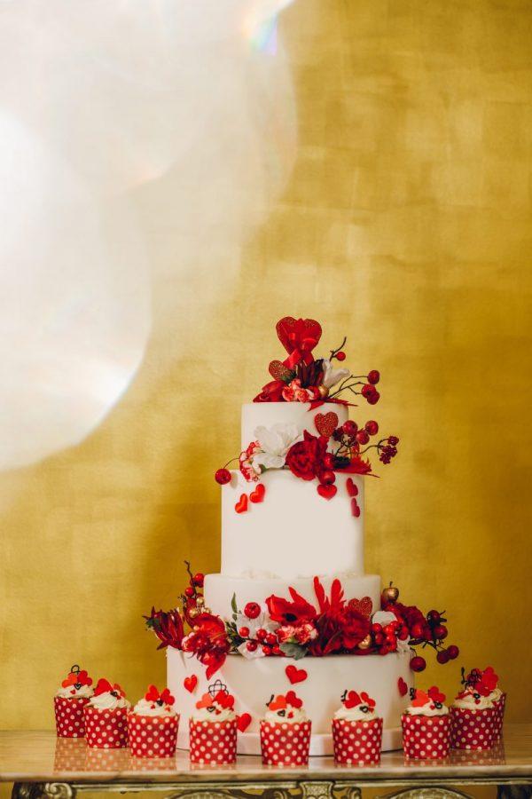 In questa foto uno sweet table nei toni del rosso con wedding cake e cupcake