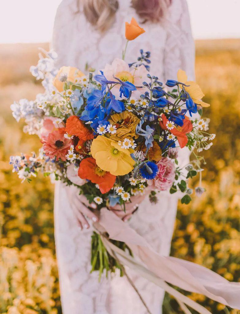 In questa foto un bouquet sposa 2021 estivo con un mix di fiori colorati.