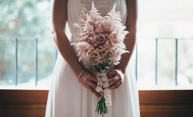 In questa foto una sposa tiene in mano il suo mazzo di astilbe, la novità in fatto di bouquet sposa 2021